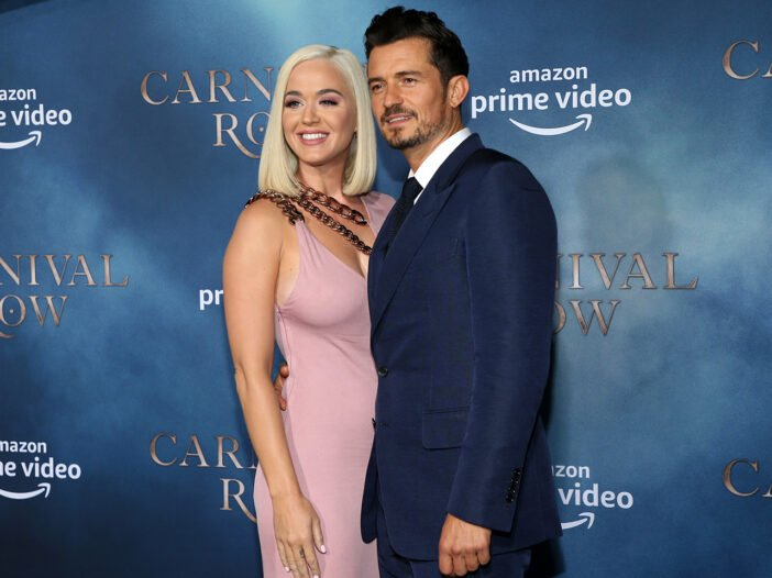 Katy Perry on the left, in a pink dress, Orlando Bloom on the right in a suit, smiling together.