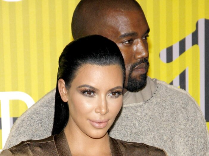 Kanye West stands behind Kim Kardashian at an MTV event