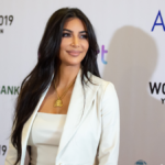 Kim Kardashian wears a white suit jacket over a white top against a white background