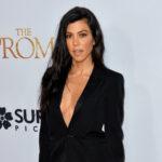Kourtney Kardashian i a low cut black top.