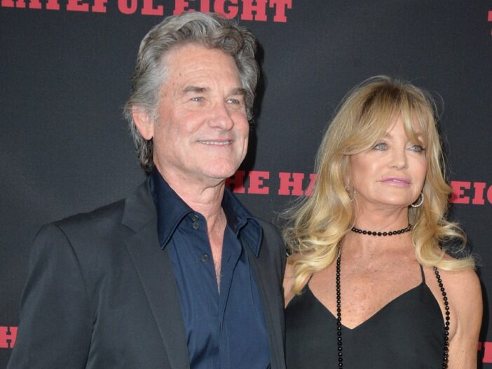 Kurt Russell stands with Goldie Hawn on the red carpet at a movie premiere