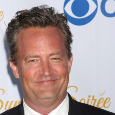 Matthew Perry wears a black suit against a white background on the red carpet