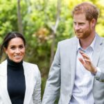 Meghan Markle, in a dark top and white blazer, walks hand in hand with Prince Harry, in a white shirt and gray blazer
