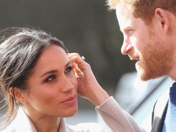 Meghan Markle and Prince Harry share a look as the Duke speaks
