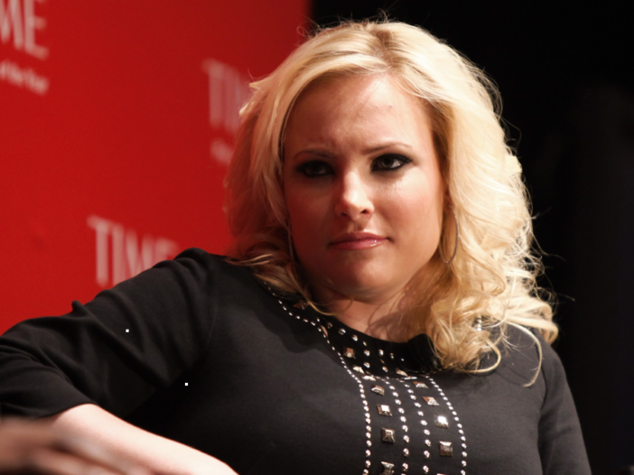 Meghan McCain listens intently while wearing a black top onstage