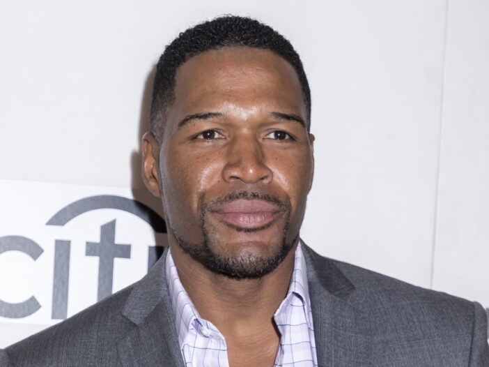 Michael Strahan wears a gray suit against a white background with grey lettering