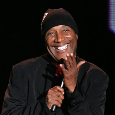 Paul Mooney smiles on stage while wearing a black jacket