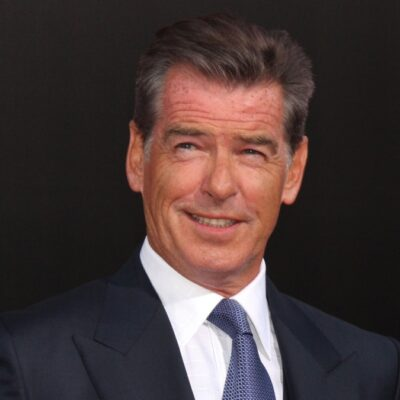 Pierce Brosnan wears a dark suit while posing in front of a black background with red lettering