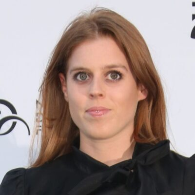 Princess Beatrice wears a black dress against a white background