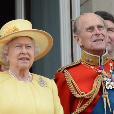 Queen Elizabeth wears a yellow dress as she stands next to Prince Philip, in his military outfit