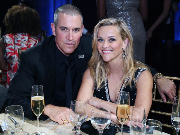 Jim Toth (left) sitting at a dinner table with Reese Witherspoon