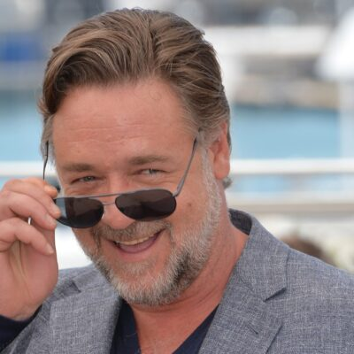 Russell Crowe cheekily lowers his sunglasses while at a film festival