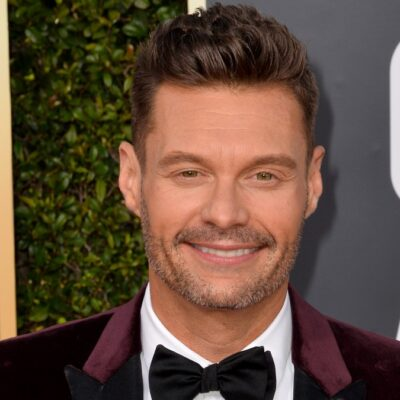 Ryan Seacrest wears a burgundy suit on the red carpet