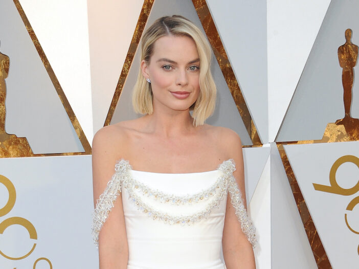 Margot Robbie smiling in a white dress