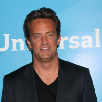 Matthew Perry smiling in a coat and shirt