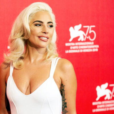 Lady Gaga smiling in a white dress