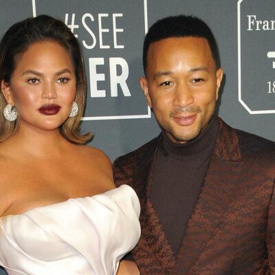 John Legend in a brown suit with Chrissy Teigen in a white dress
