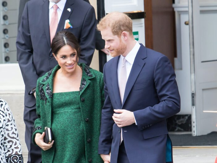 Meghan Markle in a green dress with Prince Harry in a navy suit