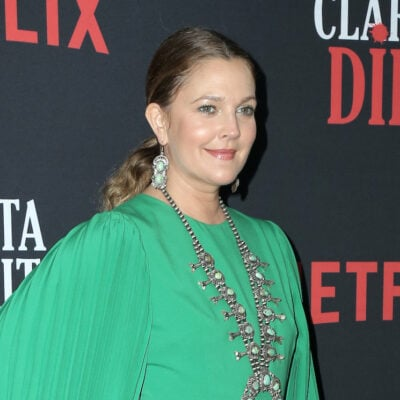 Drew Barrymore smiling in a green outfit