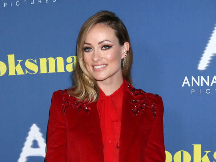 Olivia WIlde smiling in a red pantsuit