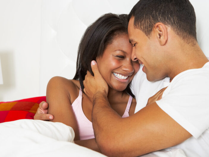 Couple smiling and laying in bed together.