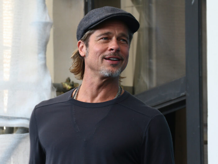 Brad Pitt smiling in a grey shirt
