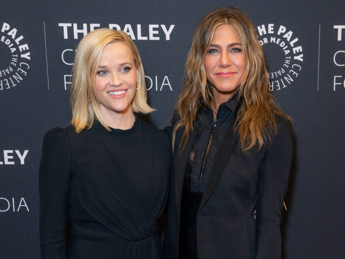 Reese Witherspoon and Jennifer Aniston smiling in black outfits