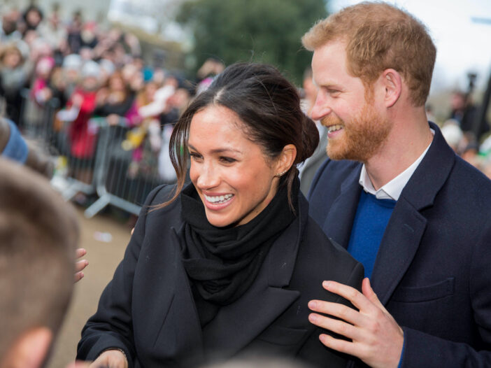Meghan Markle and Prince Harry smiling outside
