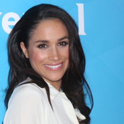 Meghan Markle smiling in a white outfit
