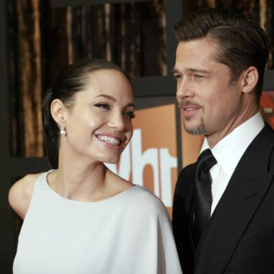 Angelina Jolie smiling in a white dress with Brad Pitt in a suit