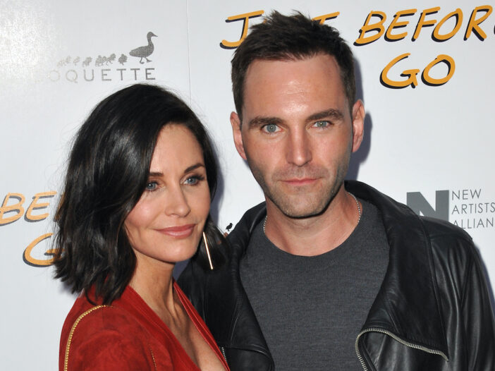 Courteney Cox in a red dress with Johnny McDaid