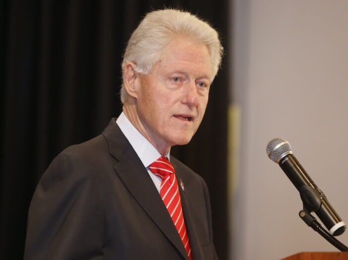 Bill Clinton in a black jacket and red tie speaking into a microphone