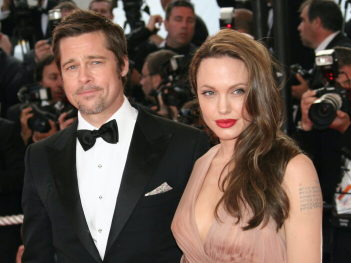 Brad Pitt in tuxedo with Angelina Jolie in a tan dress