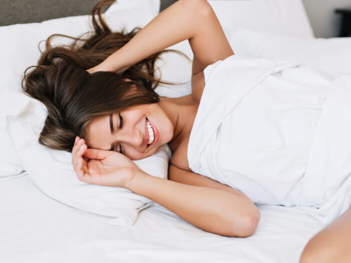 Stock photo of a woman in bed smiling.