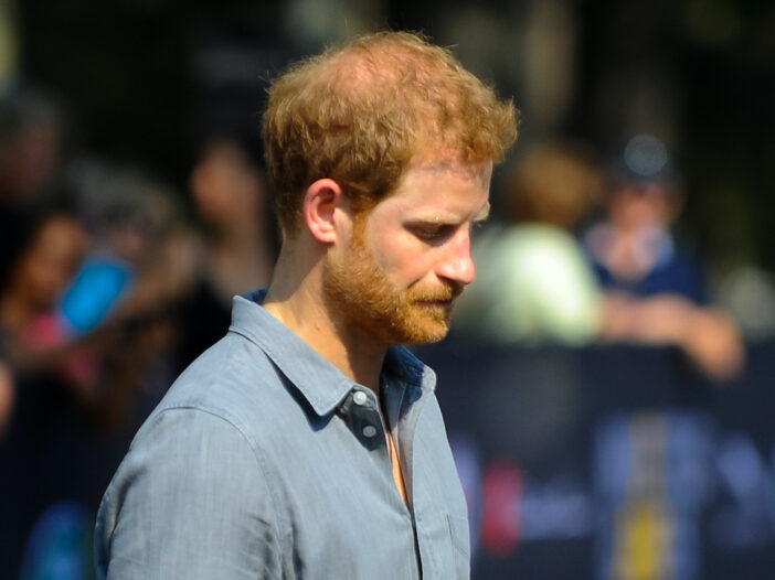 Prince Harry looking down in a blue shirt