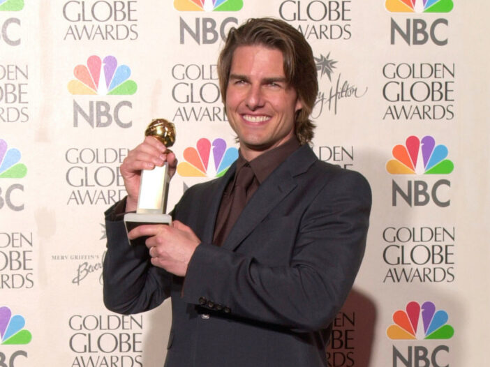 Tom Cruise holding up a Golden Globe