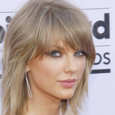 Taylor Swift looks over her shoulder at the camera while wearing a white dress