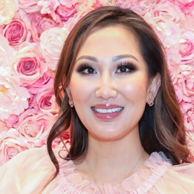 Tiffany Moon wears a gauzy pink top against a background of pink flowers