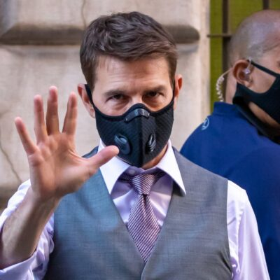 Tom Cruise raises a hand in greeting, his face covered by a black mask, on the set ot his latest film