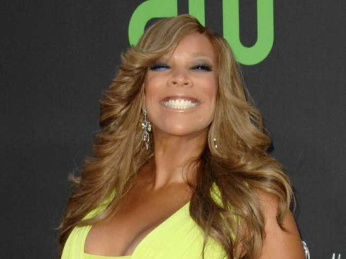 Wendy Williams wears a bright neon yellow dress against a dark backdrop