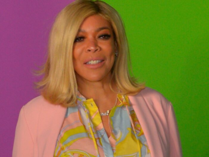 Wendy Williams stands against a purple and green background while wearing a pink top