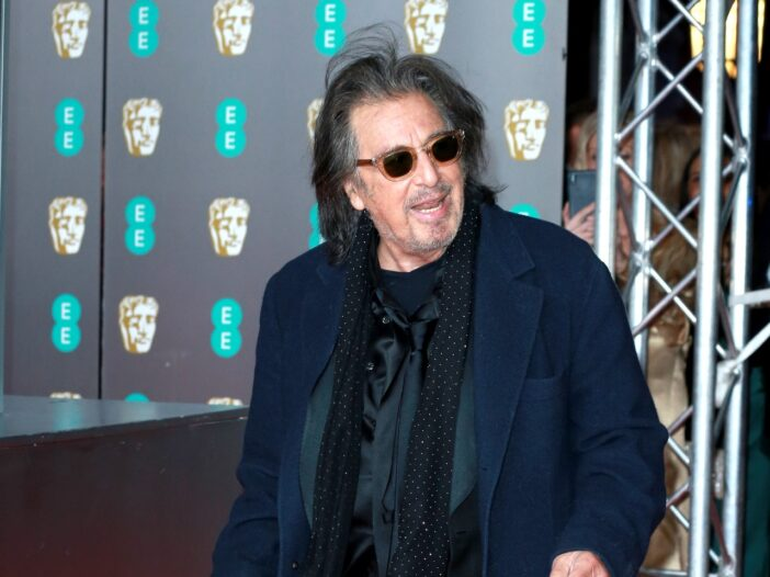 Al Pacino standing with his mouth open and wearing a blue jacket, black sunglasses, and a black scarf.