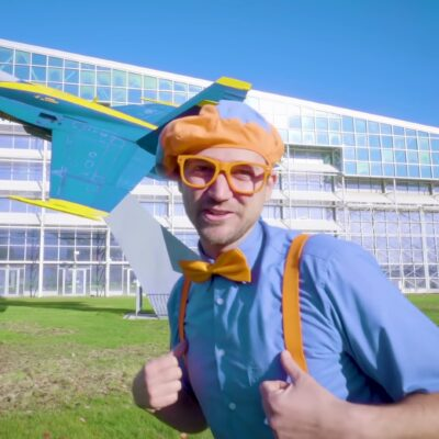 Blippi wearing a blue short, orange suspenders, orange bow tie, and a matching beret while standing in front of a blue airplane.