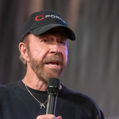 Chuck Norris wearing a black sweater and black hat, speaking into a microphone.