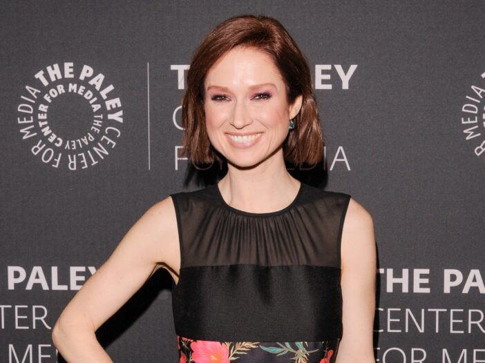 Ellie Kemper smiling and holding her hand on her hip; she's wearing a black dress with a floral design.