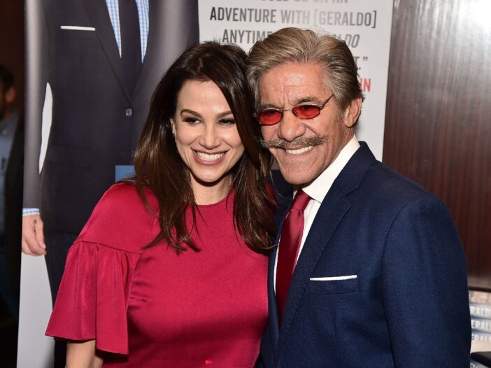 Erica Michelle Levy in a red dress smiling with her husband, Geraldo Rivera, who is wearing a navy blue suit.
