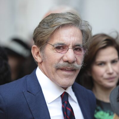 Geraldo Rivera in a crowd of people wearing a navy blue suit.
