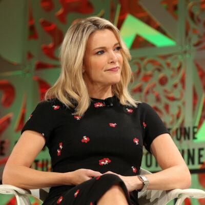 Megyn Kelly in a black dress sitting on stage