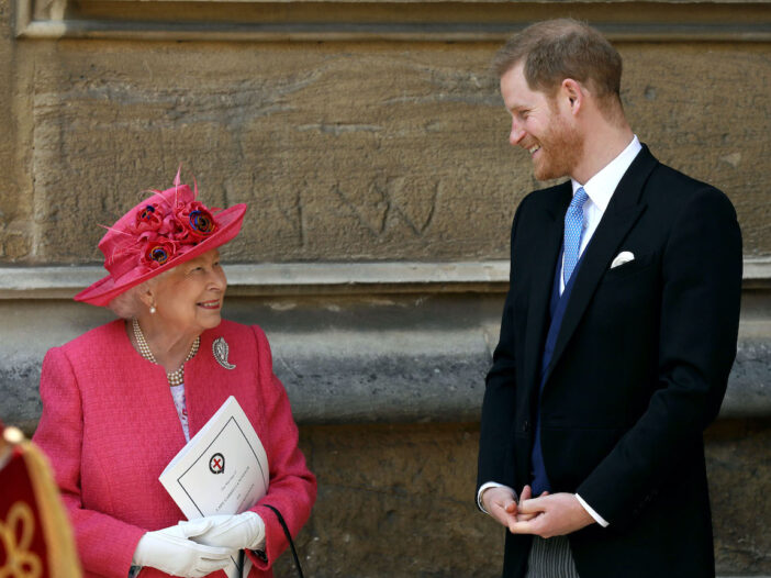Queen Elizabeth in pink smiling with Prince Harry in a suit