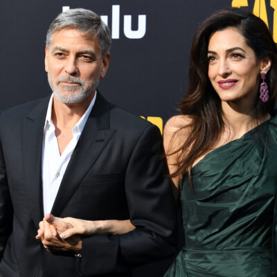 George Clooney in a suit holding hands with Amal Clooney in a green dress